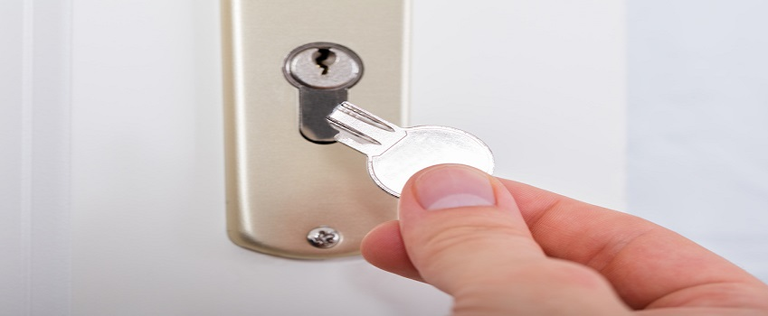 Close-up Of Person's Hand Holding Broken Key Inserting In Keyhole