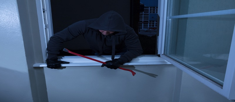 Burglar With A Crowbar Entering In A Room Through A Window